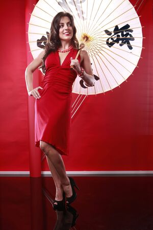 Cute brunette holding chinese umbrella on red Stock Photo - 5747833
