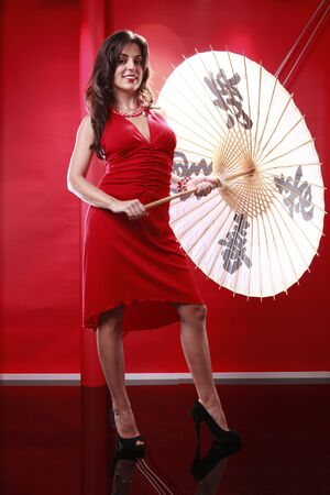 Cute brunette holding chinese umbrella on red Stock Photo - 5747837