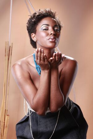 Cute black girl dressed in grey on beige Stock Photo - 5769154