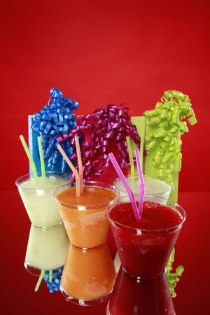 Colorful kids party smoothies and gift bags on red photo