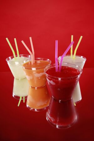 Lime, orange, vanilla and strawberry smoothies in plastic cups photo