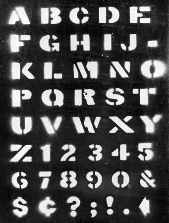 Applied paint with stencil alphabet on black photo