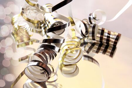 Curly serpentines cascading on a mirror on white Stock Photo