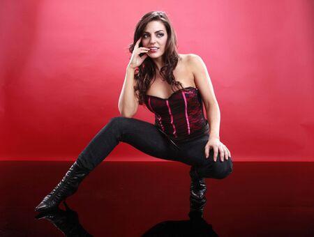 agachado: Tiro completa de una morena sexy eludido mientras vestidos con cors� y jeans