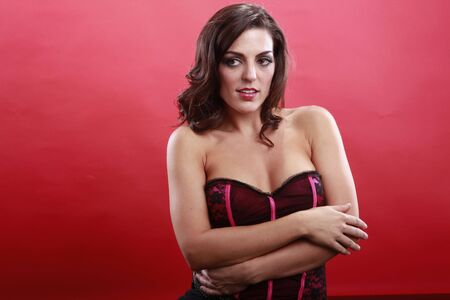 red corset: Medium horizontal shot of cute brunette in red corset on red
