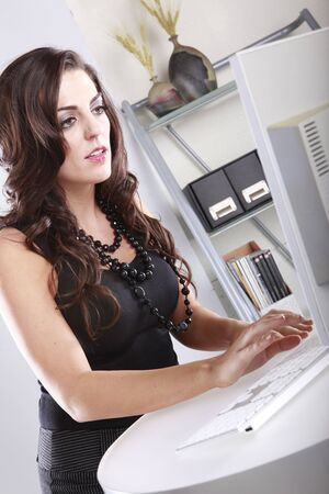 Cute brunette manager hands on her keyboard photo