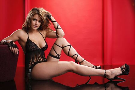 Cute blonde in sexy stringed black lingerie on red photo
