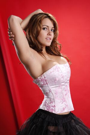 Cute blonde in sexy pink corset standing on red photo