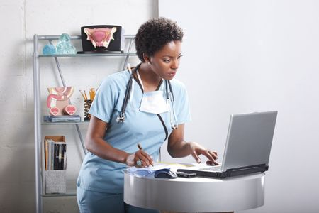 female nurse: Cute afro-american doctor at her office Stock Photo