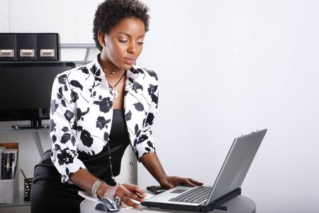 Cute executive interacts with her computer Stock Photo - 6593908