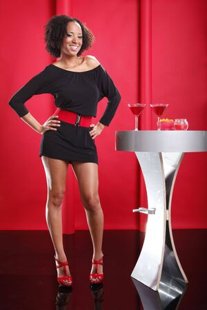 Little black dress on red lounge and Cosmopolitan cocktail photo