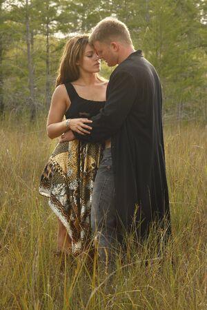 enamorados besandose: Pareja de enamorados en hierba silvestre