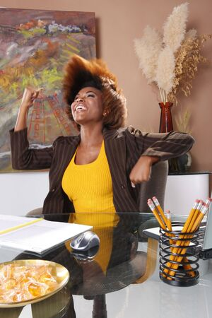 Corporate executive claims victory at her desk Stock Photo - 7216767