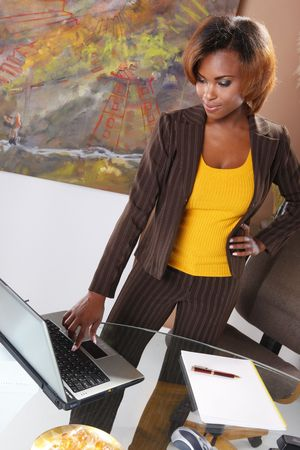 Cute executive standing at her desk Stock Photo - 7216770