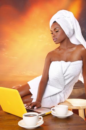 woman in towel: Cute girl gets her email while having her morning coffee Stock Photo