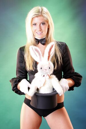 Cute magician and bunny popping out her top hat photo
