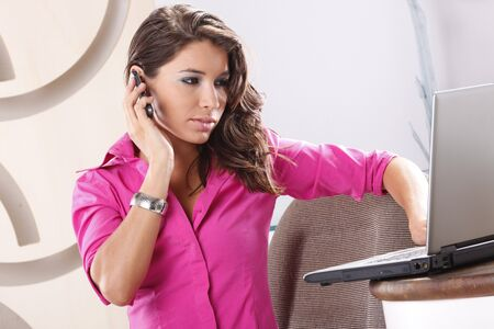 Young worker calling while browsing her laptop photo