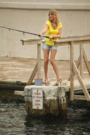 Blond takes her fishing gear to the dock photo