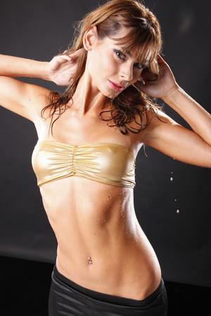 spandex: Wet golden girl on black background
