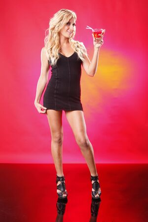 Little black dress and Cosmopolitan cocktail on red photo