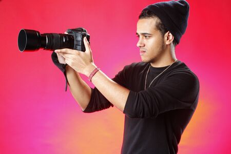 Young photographer on red background photo