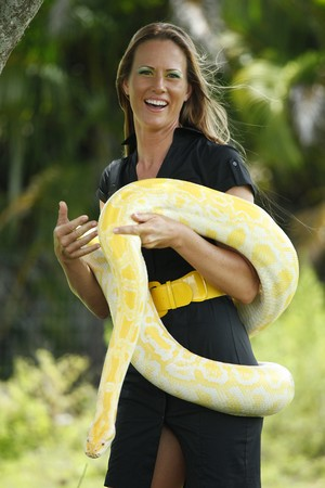 Young woman plays with a albino burmese python photo