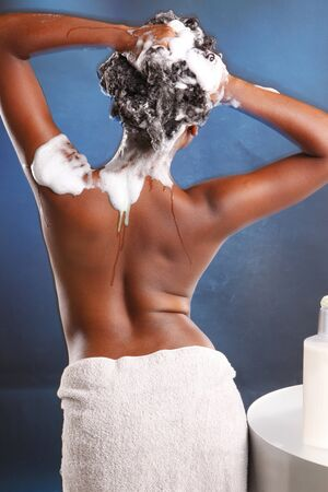 Cute African American washes her hair and turns her back to the camera Stockfoto