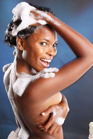 headshoot: Cute African American washes her hair and turns her back to the camera Stock Photo
