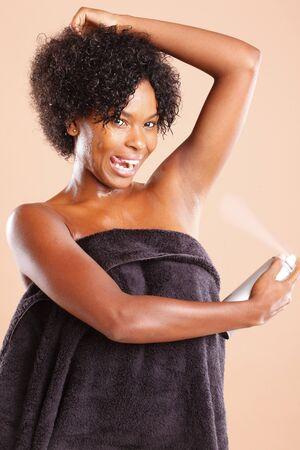 Cute Afican American using green aerosol deodorant photo