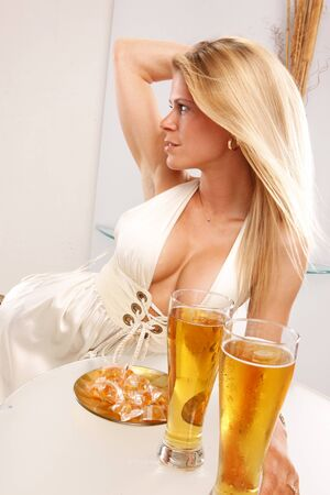 Cute blond enjoys a cold beer at a table photo