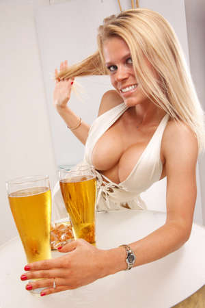 pilsner: Cute blond enjoys a cold beer at a table Stock Photo
