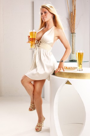 Cute blond quenches her thirst with a tall cool beer photo