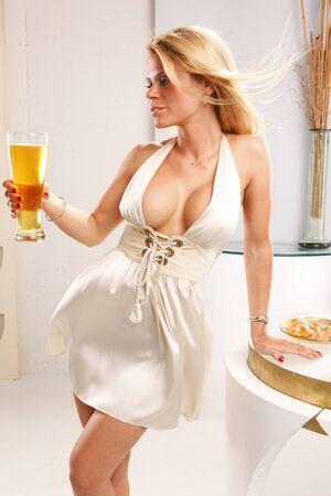 pilsner: Cute blond apaga su sed con una cerveza fr�a altura  Foto de archivo