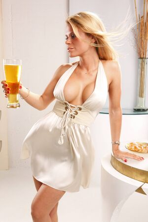 lounge bar: Cute blond quenches her thirst with a tall cool beer Stock Photo