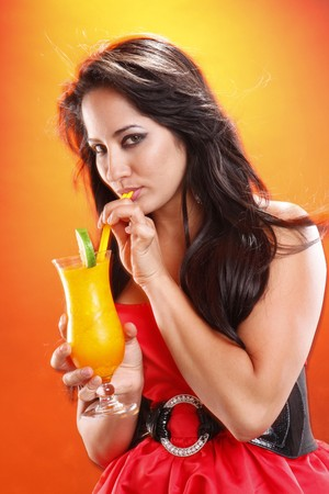 sipping: Cute brunette sipping a mango daiquiri cocktail Stock Photo