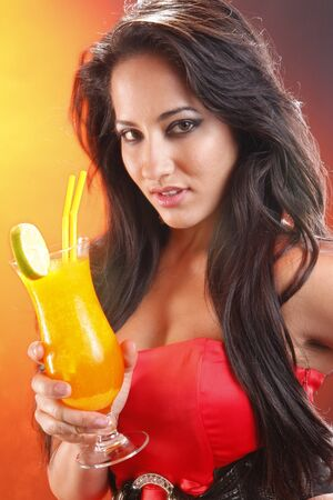 Cute brunette sipping a mango daiquiri cocktail photo