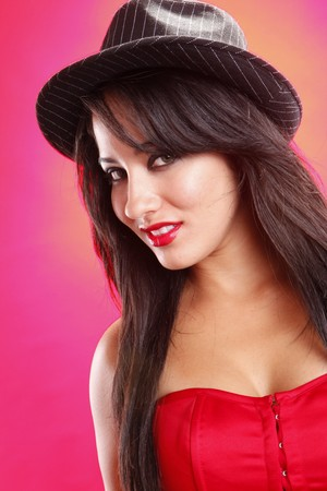 Cute brunette on red wearing a hat photo
