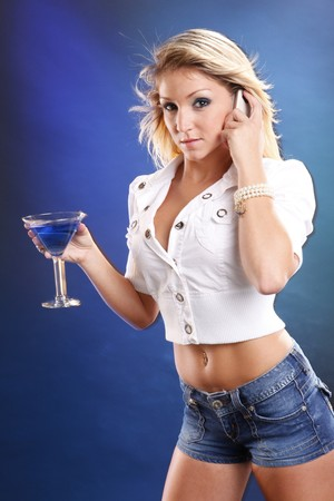 Cute blond in jeans enjoys a Blue Kamikaze cocktail photo
