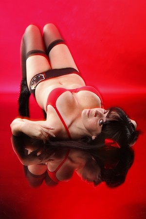 busty: Pretty brunette lays on red