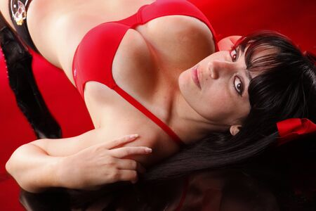 busty woman: Pretty brunette lays on red