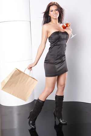Sriking brunette holds a cocktail glass and shopping bag photo