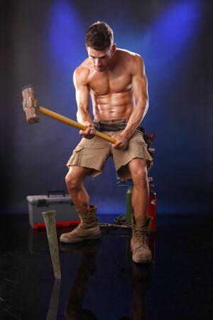 Muscular worker nailing it down 版權商用圖片