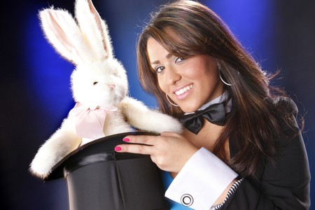 Cute magician and plush bunny out of her top hat photo