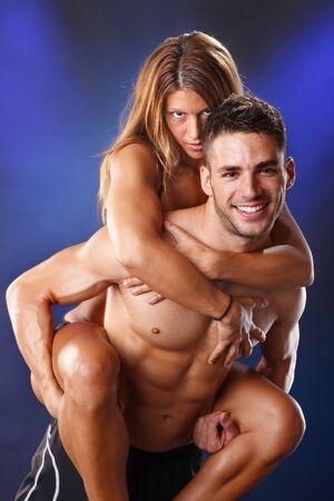 Happy toned couple piggyback riding photo