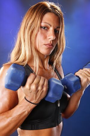 Toned blond working out with dumbbells photo