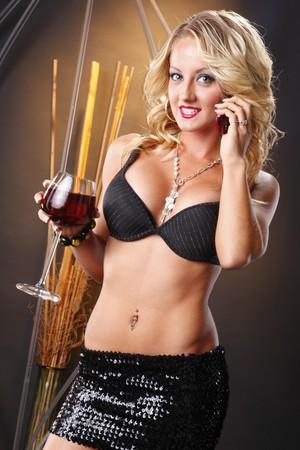 かわいいブロンドの携帯電話の呼び出しとワイン
