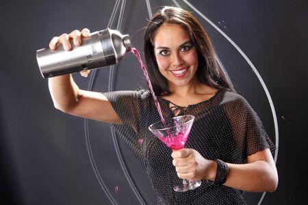 martini shaker: Young brunette prepares a pink martini