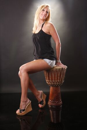Cute blond sitting on an African drum photo
