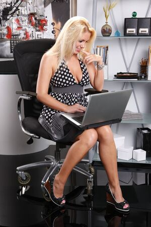 Sexy blond works with her laptop photo