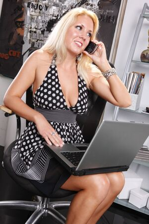 Sexy blond works with her laptop and cellphone Stock Photo